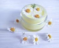 Flor de la manzanilla, crema natural de la crema hidratante de la higiene cosmética del tratamiento en un fondo de madera foto de archivo libre de regalías