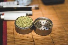 Flor de la marijuana en amoladora del metal Foto de archivo libre de regalías