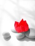Flor de loto roja, origami de papel con los guijarros Foto de archivo libre de regalías