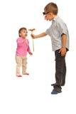 Flor de ofrecimiento del muchacho a la pequeña muchacha Foto de archivo