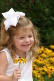 Flor de sorriso da terra arrendada da menina imagem de stock