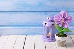 Flor decorativa en pote y vela en linterna en b de madera azul Fotografía de archivo libre de regalías