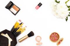 Flor del crisantemo, cepillos, sombra de ojos y otros accesorios del maquillaje en el fondo blanco El concepto de belleza Visión  Foto de archivo libre de regalías