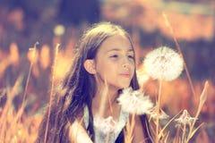 Flor del diente de león de la muchacha que sopla feliz Imagenes de archivo