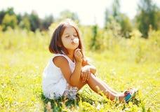 Flor del diente de león del niño lindo de la niña que sopla en verano soleado Fotografía de archivo