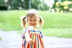 Flor del diente de león de la pequeña muchacha que sopla fotos de archivo libres de regalías
