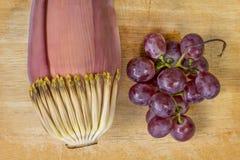 Flor del plátano y uva púrpura en la madera Imagenes de archivo