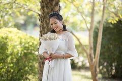 A flor do ramalhete da posse das mulheres contente admira Imagem de Stock Royalty Free
