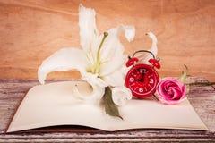 Flor e relógio de Lilly no livro de nota Fotos de Stock Royalty Free