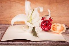 Flor e relógio de Lilly no livro de nota Fotografia de Stock
