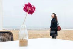 Flor encaracolado do café da praia da neve da costa do humor do cabelo longo do revestimento da mola do sorriso da mulher do retr imagem de stock