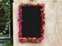 Flor enmarcada alrededor de la pizarra en la pared de piedra Foto de archivo libre de regalías