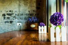 Flor falsa púrpura en maceta en la tienda del café Fotografía de archivo