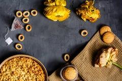 Flor, galletas amarillas y empanada de manzana que miente en fondo gris Endecha plana Visión superior imagen de archivo