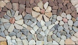 flor hecha con las piedras en la pared Fotos de archivo
