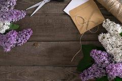 Flor lilás no fundo de madeira rústico com espaço vazio para a mensagem de cumprimento Tesouras, carretel da linha, envelope pequ Imagens de Stock