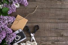 Flor lilás no fundo de madeira rústico com espaço vazio para a mensagem de cumprimento Tesouras, carretel da linha, envelope pequ Foto de Stock