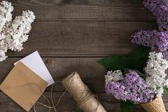 Flor lilás no fundo de madeira rústico com espaço vazio para a mensagem de cumprimento Tesouras, carretel da linha, envelope pequ Fotografia de Stock Royalty Free