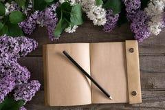 Flor lilás no fundo de madeira rústico com o caderno para a mensagem de cumprimento Vista superior Fotografia de Stock Royalty Free