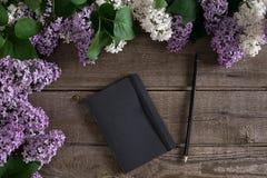 Flor lilás no fundo de madeira rústico com o caderno para a mensagem de cumprimento Vista superior Fotos de Stock