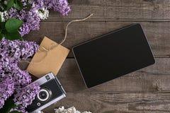 Flor lilás no fundo de madeira rústico, tabuleta com espaço vazio para a mensagem de cumprimento Tesouras, carretel da linha, peq Foto de Stock Royalty Free