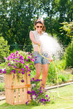 Flor molhando de sorriso da mangueira da mulher do jardim do verão Fotos de Stock Royalty Free