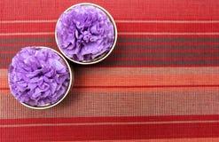 Flor púrpura en la tabla, mantel colorido como fondo Fotografía de archivo libre de regalías