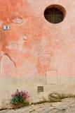 Flor, pared con una ventana redonda Imágenes de archivo libres de regalías