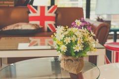 A flor plástica decora na tabela, cor pastel Fotos de Stock Royalty Free