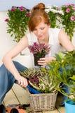 Flor potted de la mujer del redhead de la terraza del jardín del verano Imagen de archivo