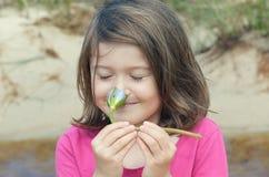 Flor que huele de la muchacha Imagen de archivo libre de regalías
