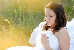 Flor que huele de la novia hermosa que miente al aire libre Imagenes de archivo