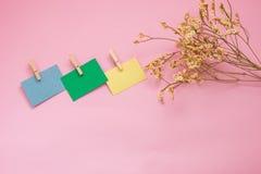 Flor que põe ao lado nota de post-it três ou nota do escritório do papel mim Foto de Stock