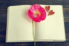 Flor rosada de la amapola en un cuaderno abierto y dos corazones decorativos Fotografía de archivo