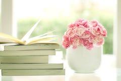 Flor rosada dulce y romántica fresca del clavel con el backg de los libros imagen de archivo