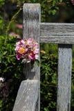 Flor rosada en banco de madera Imagenes de archivo