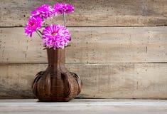flor rosada hermosa en tarro en el fondo de madera Fotos de archivo