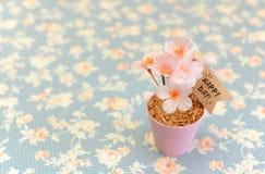 Flor rosado alegre artificial en pequeño pote de acero con día feliz Fotografía de archivo