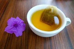 Flor salvaje púrpura de la petunia y una taza de té con la bolsita de té Imagen de archivo