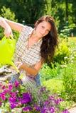 Flor sonriente de la violeta de la poder de riego de la mujer que cultiva un huerto Fotos de archivo