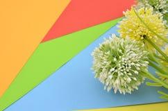 Flor verde y amarilla artificial en fondo azul, verde, rojo, anaranjado y amarillo Fotos de archivo