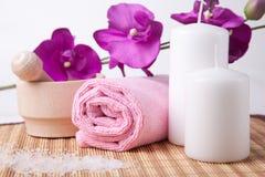 Flor y toalla rosadas con dos velas. composición del balneario Fotos de archivo