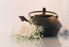 Flor y una tetera en el fondo blanco Foto de archivo