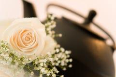 Flor y una tetera en el fondo blanco Imagen de archivo