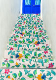 The flora painting on concrete stairway. Leading to a blue door entrance Stock Photos
