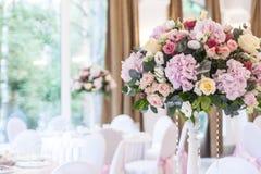 Floral ρυθμίσεις στην άσπρη στάση στυλοβατών στους πίνακες στο εστιατόριο στοκ φωτογραφίες με δικαίωμα ελεύθερης χρήσης