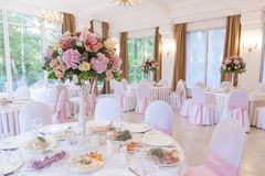 Floral ρυθμίσεις στην άσπρη στάση στυλοβατών στους πίνακες στο εστιατόριο στοκ εικόνες