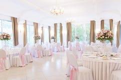 Floral ρυθμίσεις στην άσπρη στάση στυλοβατών στους πίνακες στο εστιατόριο στοκ φωτογραφία με δικαίωμα ελεύθερης χρήσης