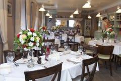 Floral στάση στυλοβατών ρυθμίσεων στους πίνακες στο εστιατόριο στοκ εικόνα με δικαίωμα ελεύθερης χρήσης