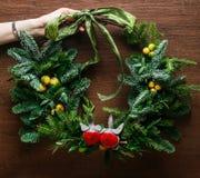 Floral διακόσμηση στεφανιών Χριστουγέννων με τα μπιχλιμπίδια, το κόκκινο τόξο, τον ελαιόπρινο και τη χειμερινή πρασινάδα πέρα από Στοκ φωτογραφία με δικαίωμα ελεύθερης χρήσης